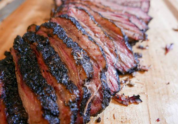 Sliced smoked brisket on a wooden cutting board. stock photo