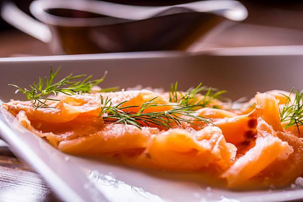 sliced smoked salmon with dressing and herb decoration. - orangenscheiben trocknen stock-fotos und bilder