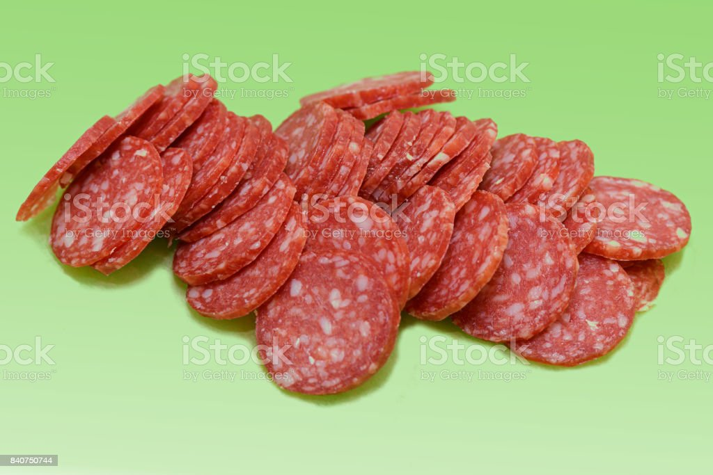 sliced smoked sausage on a green background stock photo