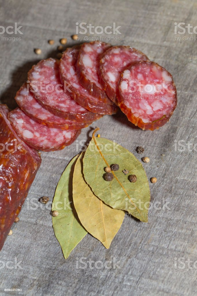 sliced smoked sausage on the wood background stock photo