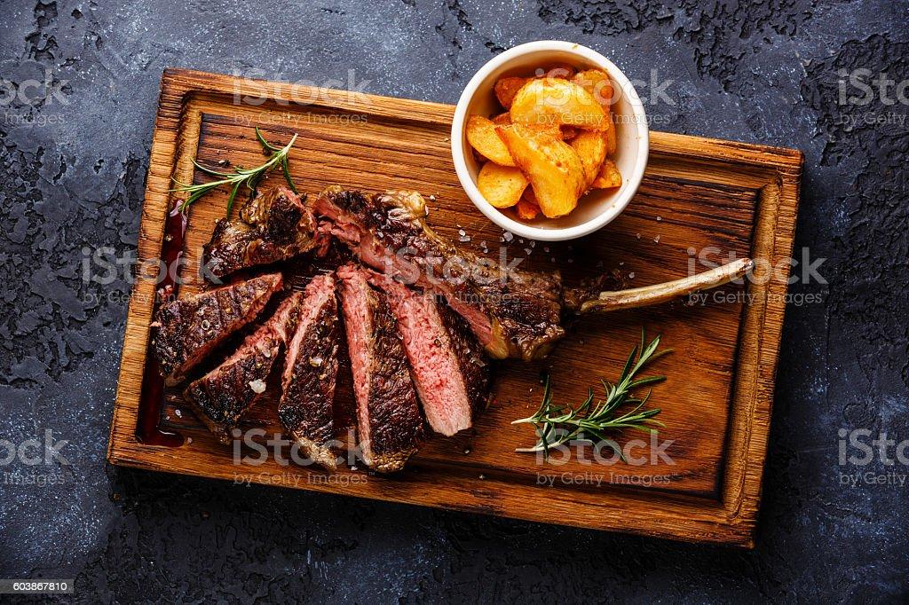 Sliced Steak on bone Veal rib with potato wedges stock photo