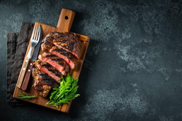 gesneden biefstuk ribeye, gegrild met peper, knoflook, zout en tijm geserveerd op een houten snijplank op een donkere stenen achtergrond. bovenste weergave met kopieer ruimte. platte lay - vleesdelen stockfoto's en -beelden