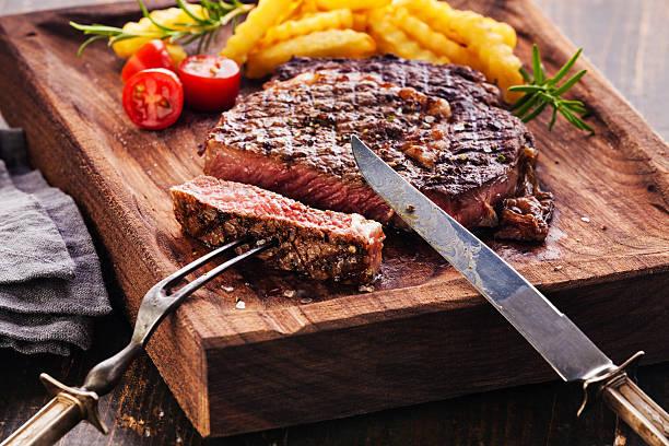 scheiben-ribeye-steak mit pommes frites - tranchieren stock-fotos und bilder