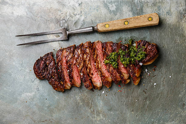 scheiben-steak mit chimichurri-sauce und fleisch gabelung - grillstein stock-fotos und bilder
