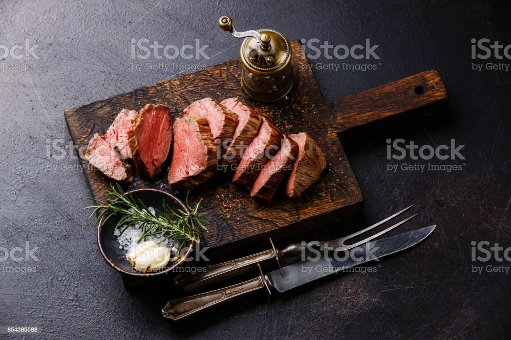 Sliced tenderloin Steak Roast beef with knife and fork carving set stock photo