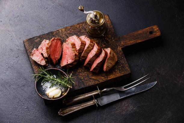 geschnittene filet steak roastbeef mit messer und gabel carving-set - tranchieren stock-fotos und bilder