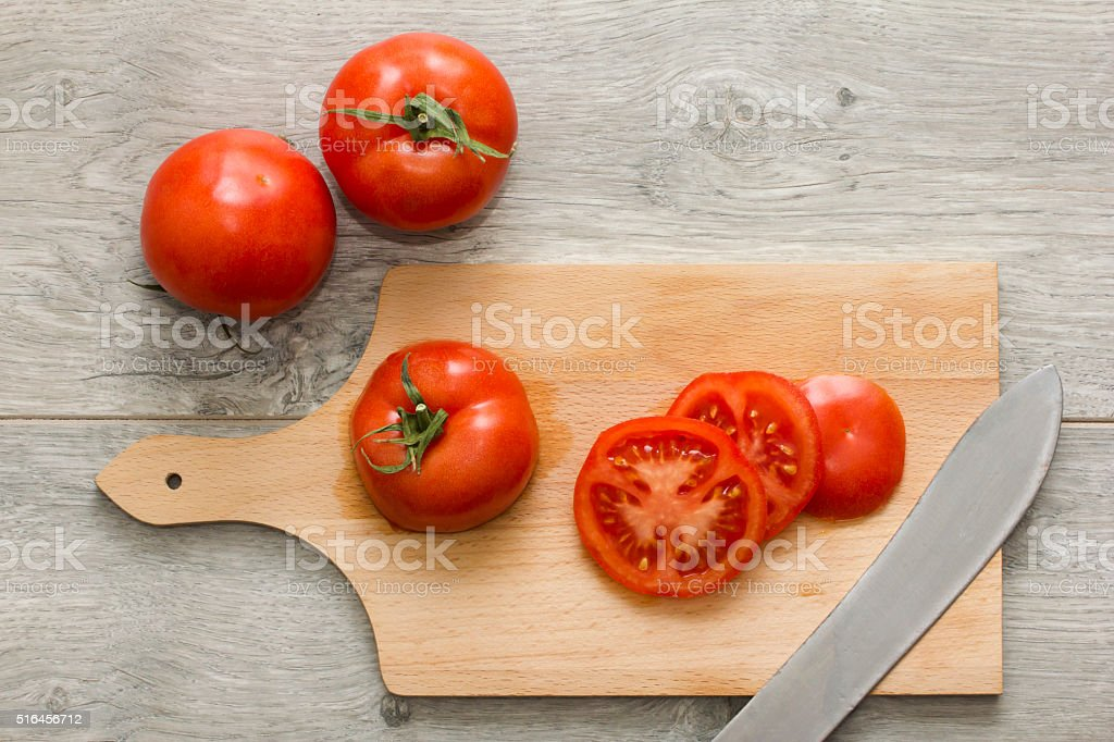 Sliced tomato on wooden kitchen table. Directly above view. stock photo