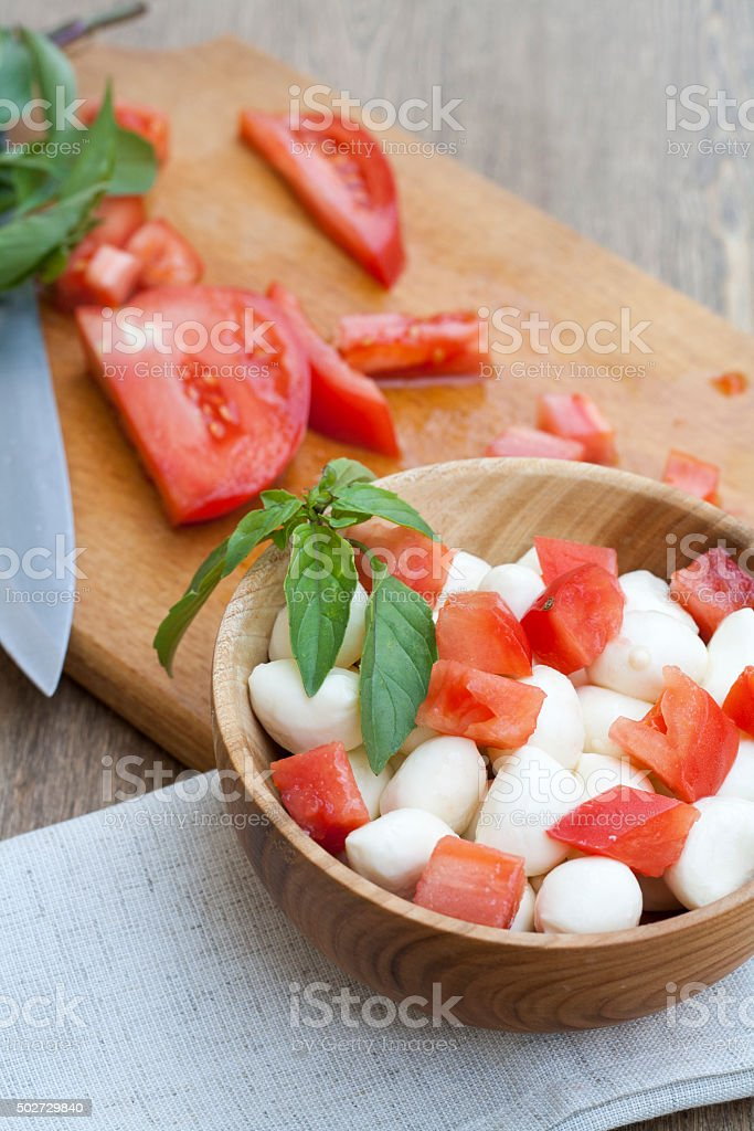 Sliced tomatoes, basil and mozzarella cheese on a wooden plate royalty-free stock photo