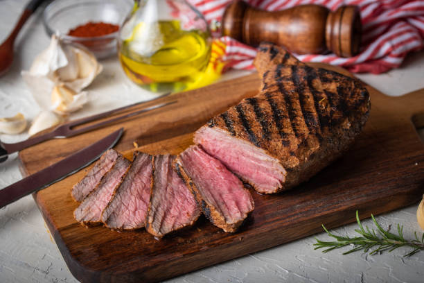 sliced tri tip seak marinated with santa maria sauce  on wooden cutting board stock photo