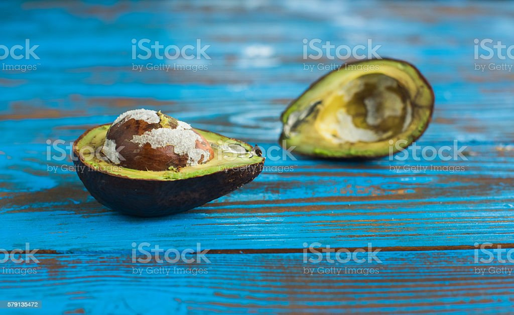 sliced unhealthy rotten avocados on old blue table stock photo