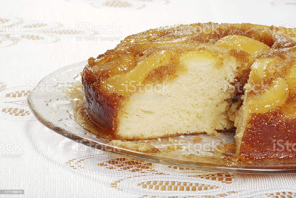 sliced upside down pear cake on glass plate stock photo