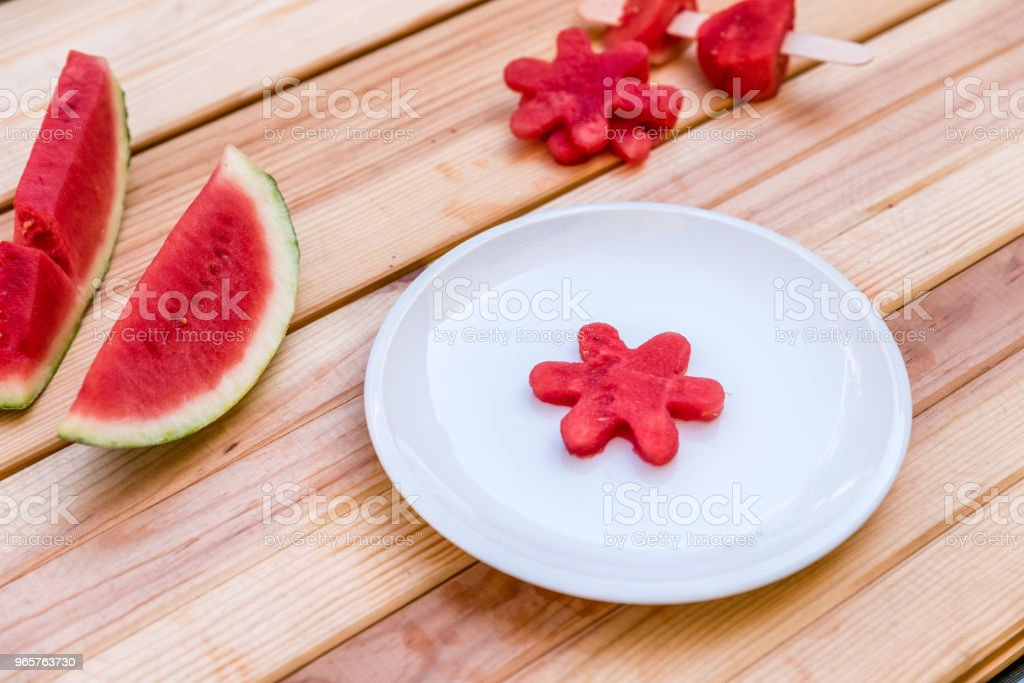 sliced ​​watermelon and a piece of watermelon shaped like a flower on a white plate on wooden table - Royalty-free Agriculture Stock Photo