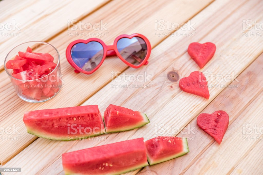 sliced watermelon, glass cup with watermelon slices and red sunglasses with heart shape on wooden table - Royalty-free Agriculture Stock Photo