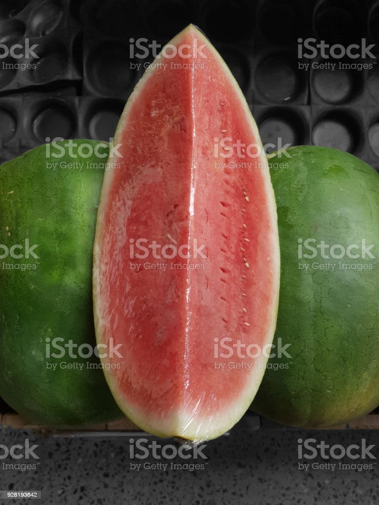 Sliced watermelon on two whole melons stock photo