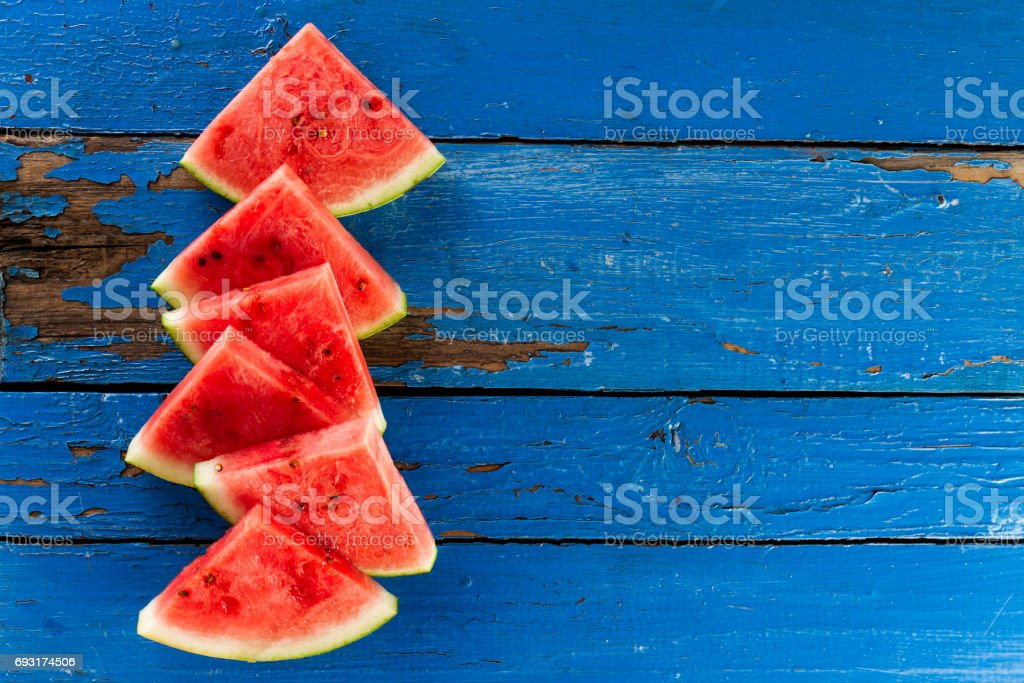 Sliced watermelon Top View. Many slices on an old rustic blue table. Side composition with copy space. Food Backrgound. stock photo
