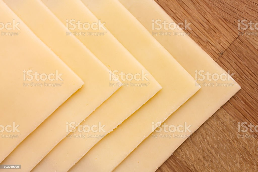 Sliced yellow sandwhich cheese neatly arranged on a wood surface. stock photo