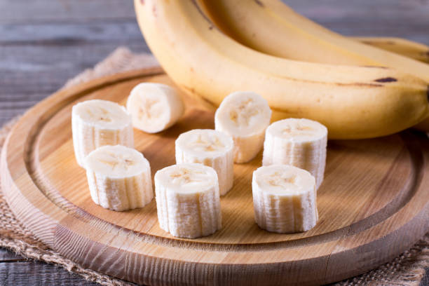 segmenten van een banaan op een snijplank op een houten tafel - kalium stockfoto's en -beelden