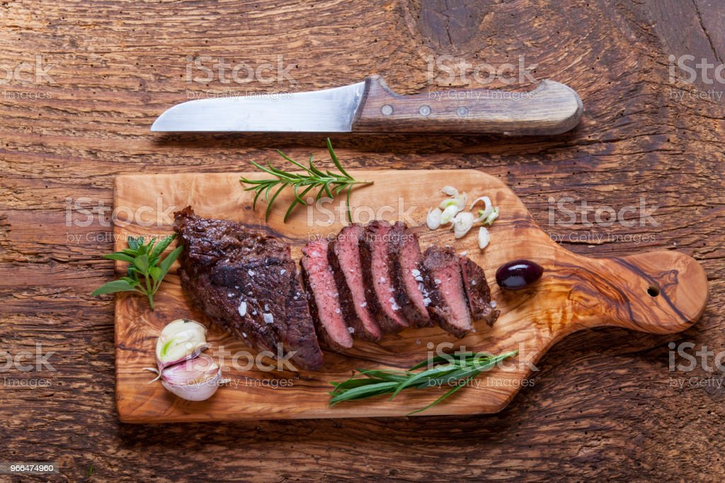 slices of a grilled steak on wood stock photo