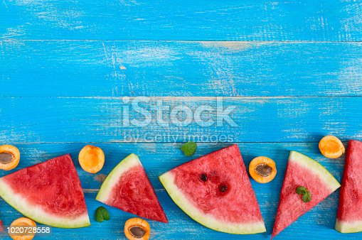 istock Slices of a ripe watermelon with mint leaves and apricot on a blue wooden background. Free space for your project. 1020728558