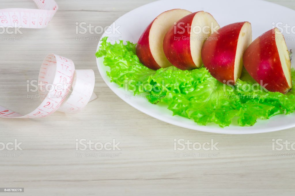 Slices of apple with green salad on the plate stock photo