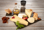 Slices of assorted French, Spanish and Italian cheese on a dark board, served with bread and dried fruit, wooden background