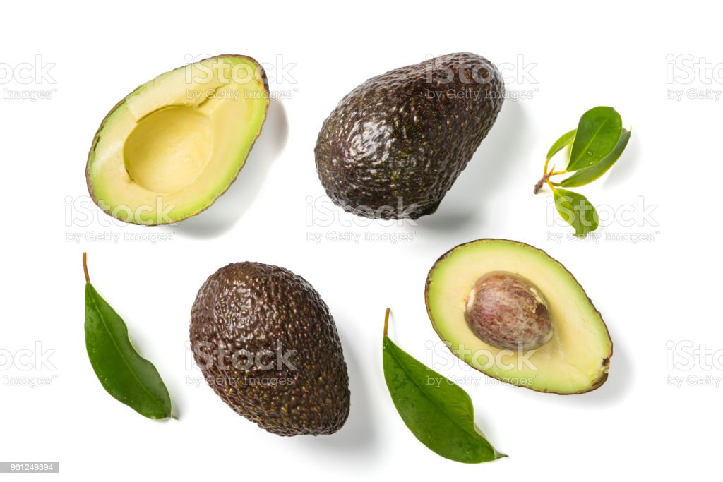 Slices of avocado on white background. Whole and half with leaves. Design element for product label stock photo