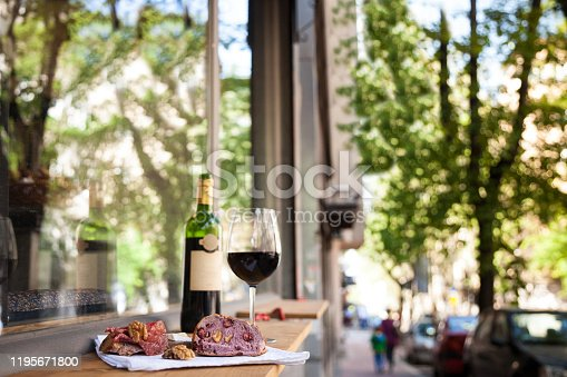 Picture of a typical French apero, or apetizer, with a bottle of French red wine, dried meat called saucisson, brie, and baguette bread on the terrace.