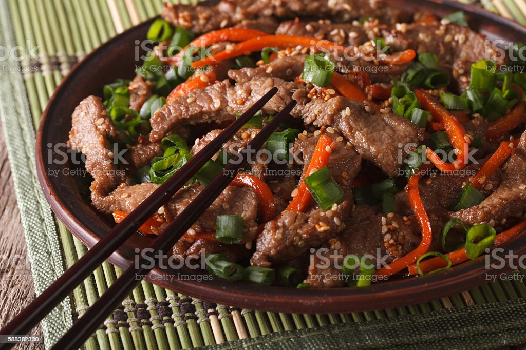 slices of beef fried with sesame seeds and carrots closeup stock photo
