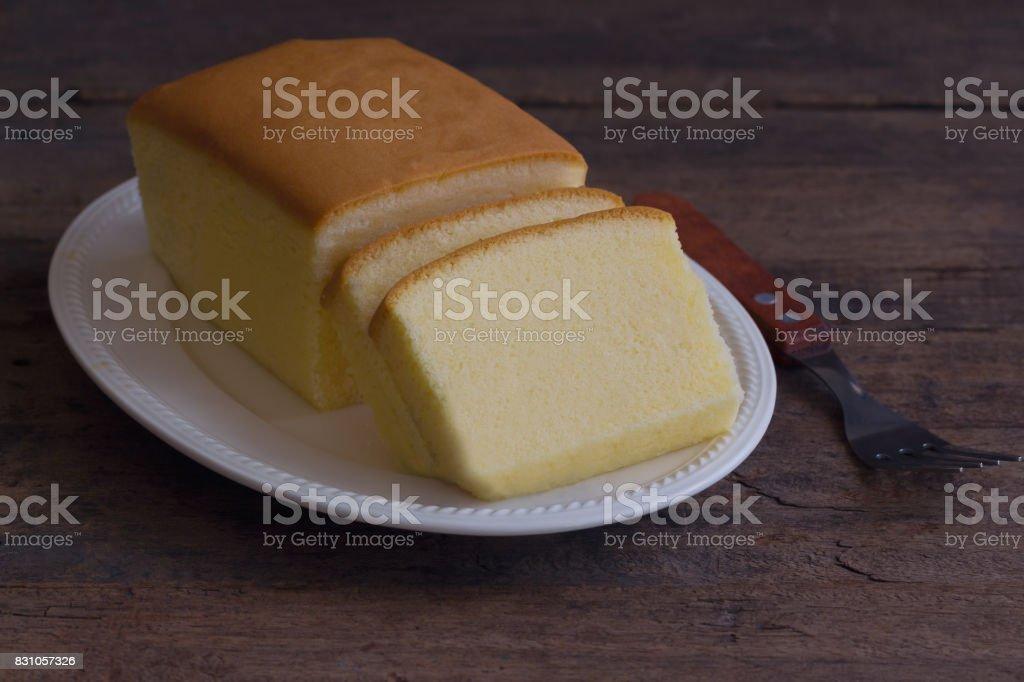 Fatias de bolo de manteiga na chapa branca. Delicioso bolo de manteiga caseira simples macio e húmido. Saboroso bolo de libra ou manteiga bolo pronto para ser servido na mesa de madeira rústica. Conceito de padaria caseiro com espaço de cópia para plano de fundo ou papel de parede. - foto de acervo