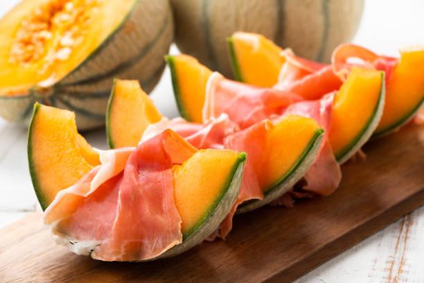 scheiben der cantaloupe-melone mit schinken - orangenscheiben trocknen stock-fotos und bilder