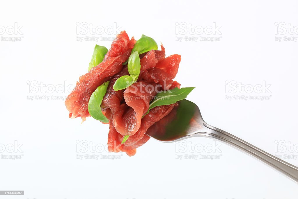 Slices of carpaccio with arugula on a fork royalty-free stock photo
