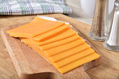 Thick slices of cheddar cheese on a wooden cutting board