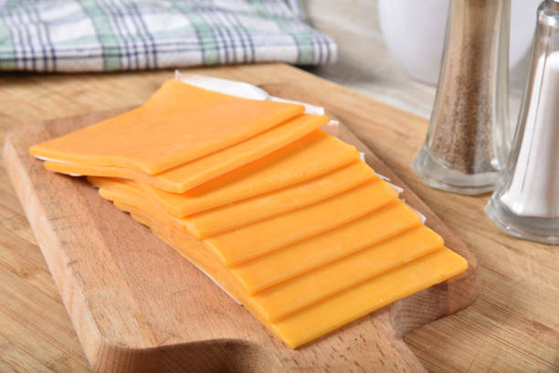 Slices of cheddar cheese on a cutting board Thick slices of cheddar cheese on a wooden cutting board cheese stock pictures, royalty-free photos & images