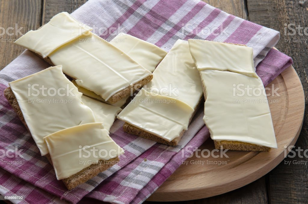 slices of cheese on bread toasts wooden background stock photo