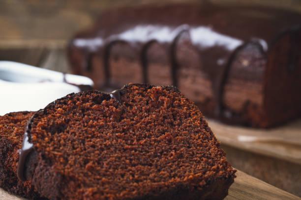 scheiben von schokoladenkuchen auf holzbrett - schokoladen biskuitkuchen stock-fotos und bilder
