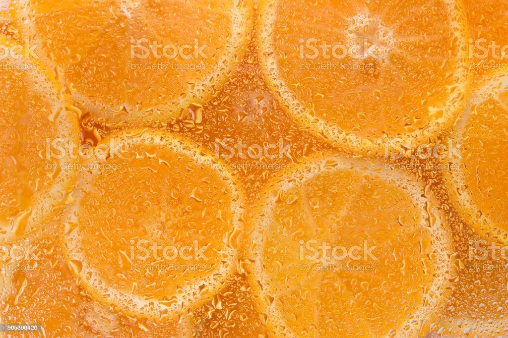 Slices of citrus through water droplets on glass, orange background, fresh fruits zbiór zdjęć royalty-free