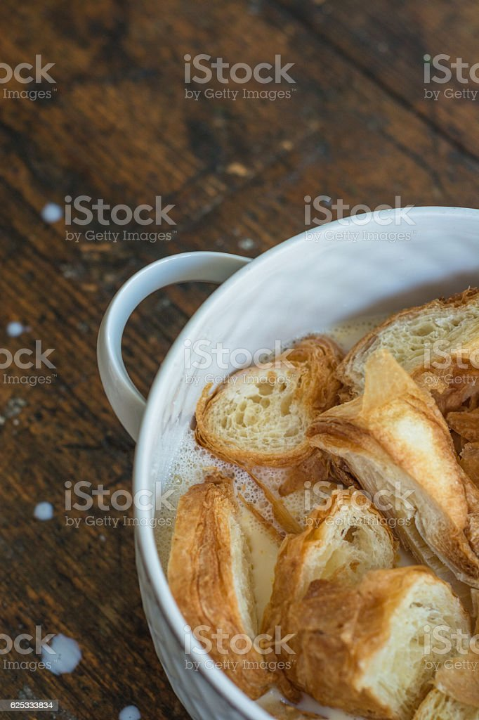 Slices of croissant in a vintage looking milk pot stock photo