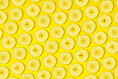 bananas pattern on yellow background. Abstract background with slices of fresh bananas.