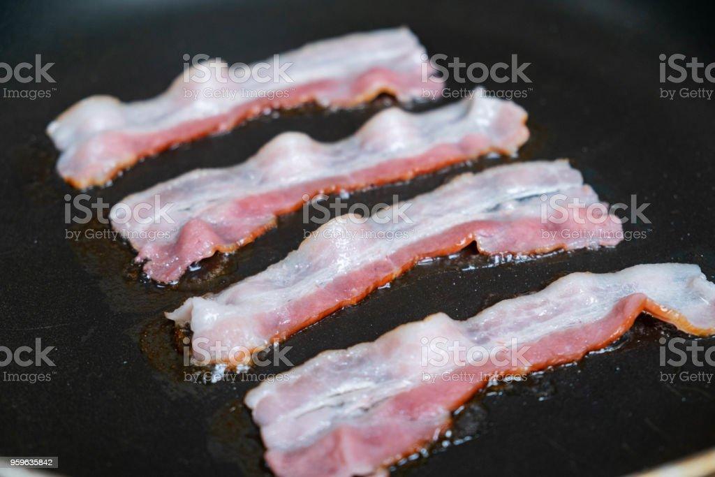 lonchas de tocino fresco frito en una sartén - Foto de stock de Alimento libre de derechos
