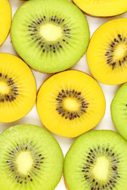 fatias de kiwi verde e amarelo fresco frutas alimentos plano de fundo - foto de acervo