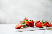 Slices of fresh strawberries on chopping board with kitchen knife. Fresh strawberries on cutting board in kitchen.