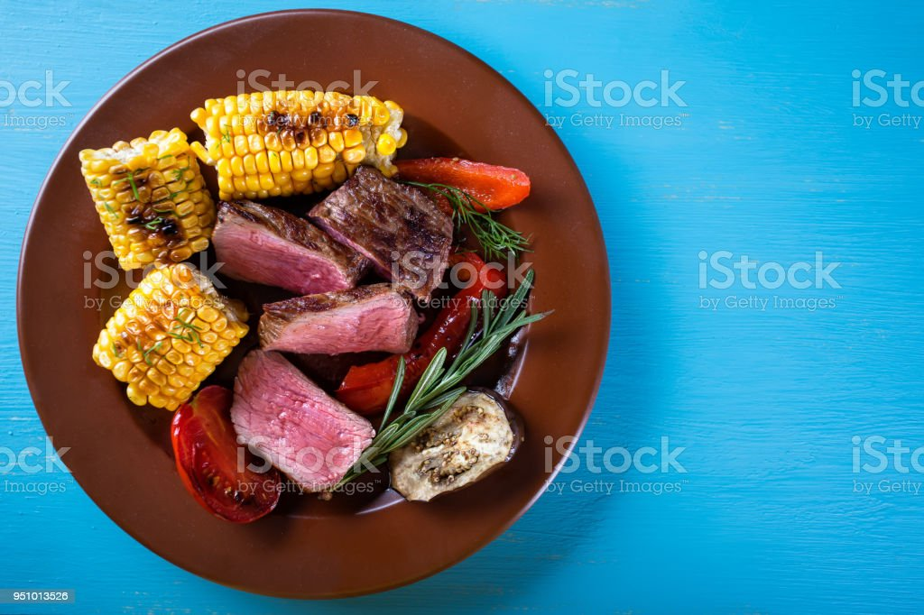 Slices of fried meat with corn and vegetables on plate stock photo