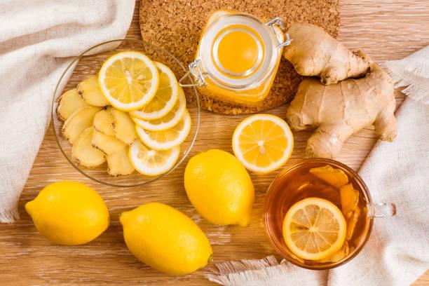 Dilim zencefil ve limon bir plaka üzerinde kavanoz bal ve ahşap bir masa üzerinde limonlu çay fincan ile stok fotoğrafı