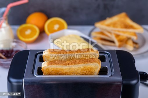 Slices of great toast coming out of the toaster. Healthy breakfast food and heating technology concept.  Focus on slice of great.