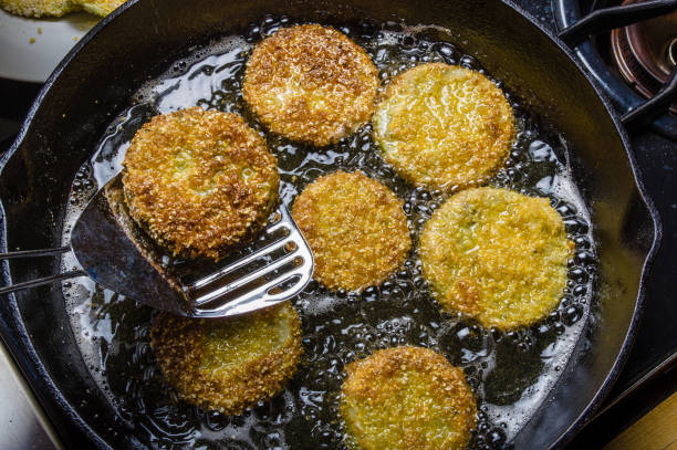 Slices of green tomato being fried stock photo