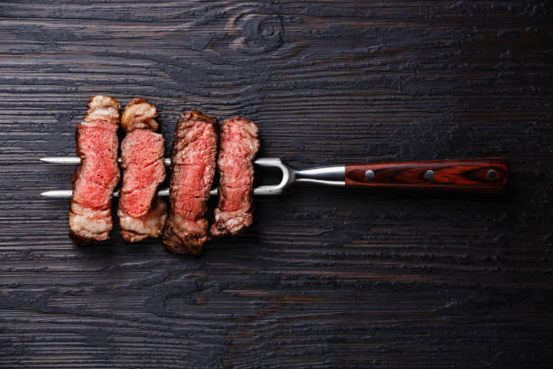 Slices of grilled meat barbecue steak Rib eye on meat fork Slices of grilled meat barbecue steak Rib eye on meat fork on burned black wooden background red meat stock pictures, royalty-free photos & images