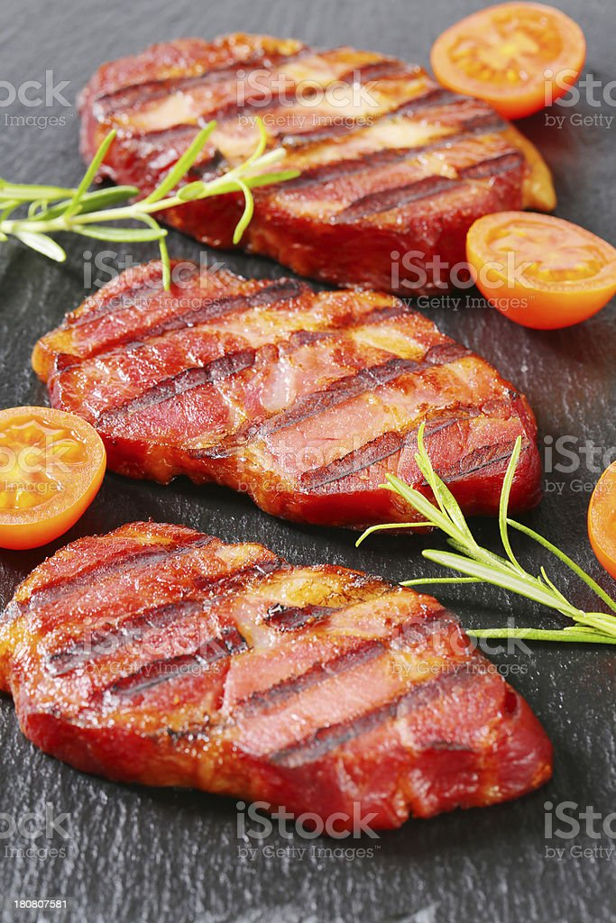 Slices of grilled pork neck on a black background royalty-free stock photo