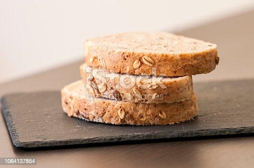 istock Slices of homemade multigrain bread on black slate board 1064137854