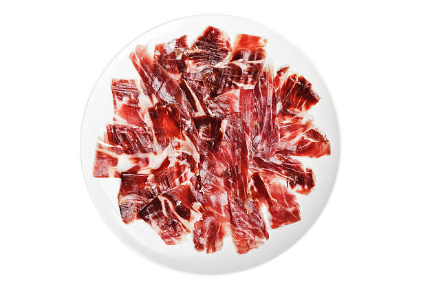 Slices of iberican ham Slices of ham cutted by hand on a white plate over a white background estudio stock pictures, royalty-free photos & images