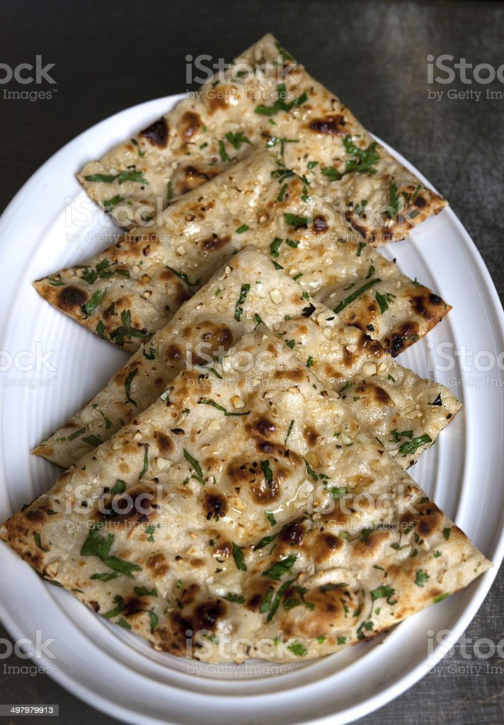 Slices of Indian flat bread Naan with garlic stock photo
